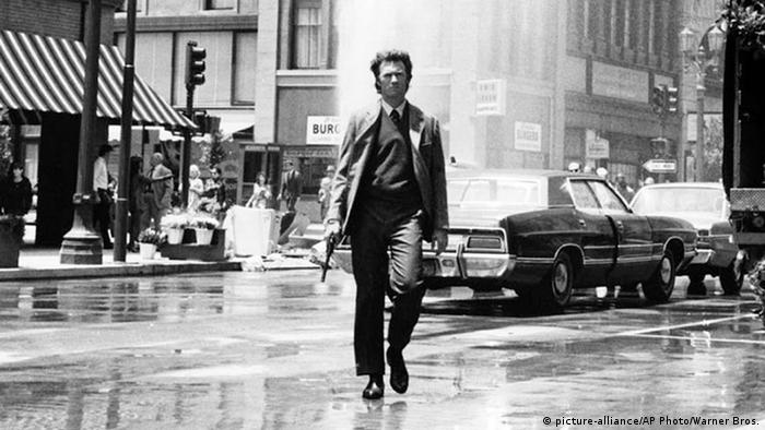 Clint Eastwood as Dirty Harry walking down the street holding a gun