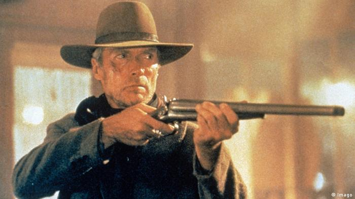 Clint Eastwood holding up a rifle in the movie Unforgiven