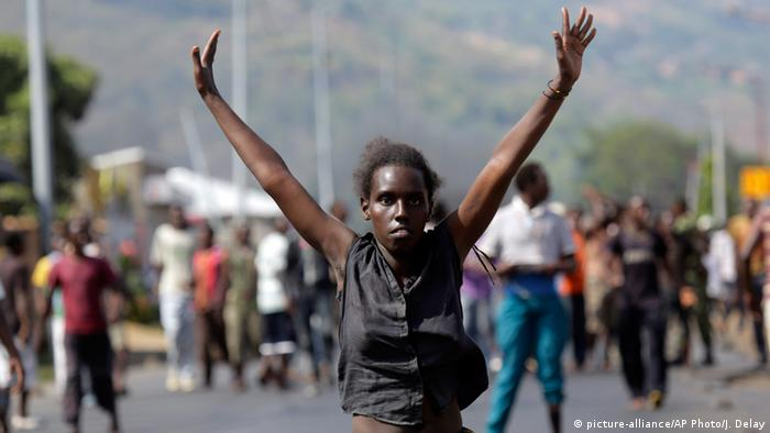 A demonstrator raises her hands in the air as she faces soldiers in the Musaga neighborhood of Bujumbura, Burundi ( AP Photo/Jerome Delay)
