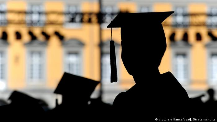 Silhouettes of graduates in cap and gown are seen in front of Bonn University