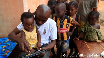 African children playing with a tablet computer.