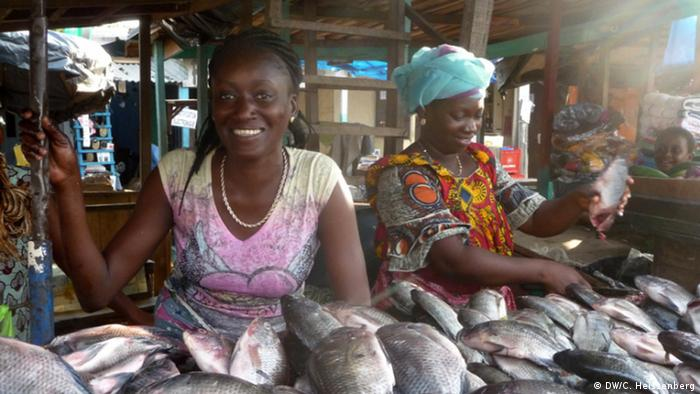 Two women selling fish at a market