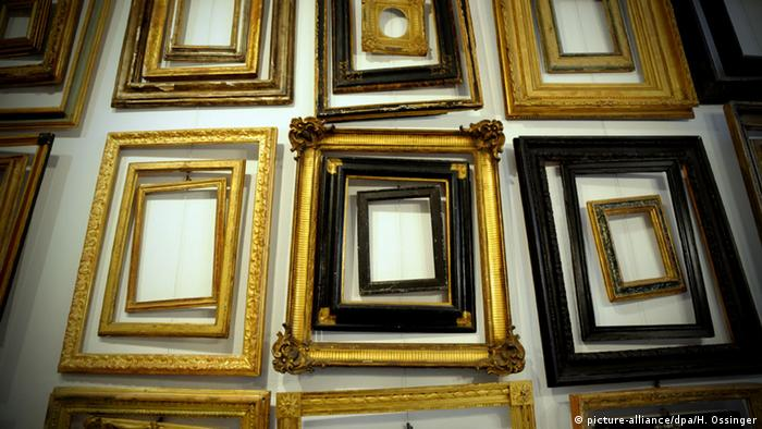 A wall of empty painting frames.
