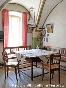 Eine Wohnstube mit einem Tisch, zwei Stühlen und einem kleinen Altar mit Kreuz in der rechten Ecke.