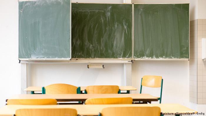 Foto mostra uma sala de aula vazia, com um quadro verde escuro com marcas de giz apagado