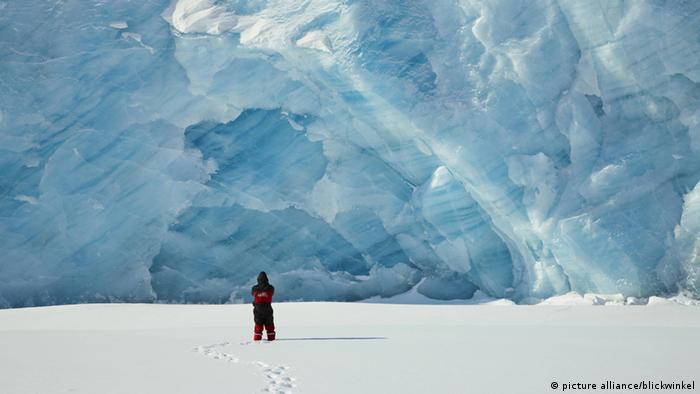 a human in front of a glacier