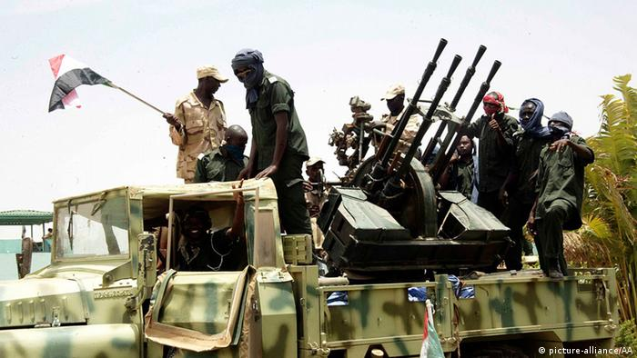 South Sudan rebels stand atop a war vehicle.