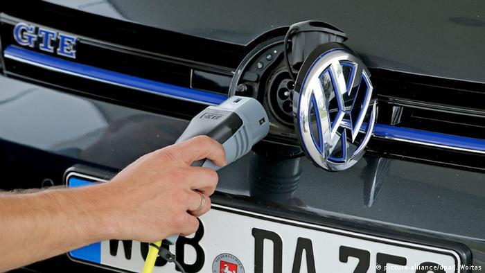 Seorang pria mengisi daya mobil listrik Volkswagen