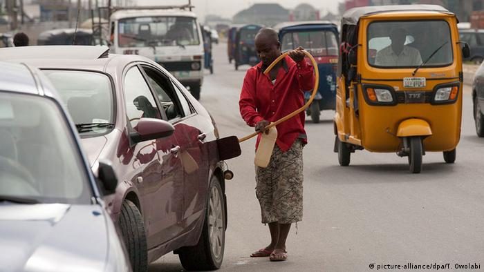 A black market oil trader supplies a car with fuel. Photo: EPA/TIFE OWOLABI