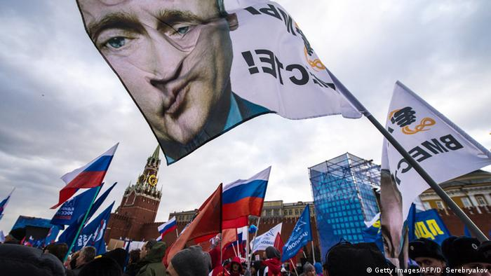 Pro-Kremlin activists rally at the Red Square in Moscow, with a flag depicting President Vladimir Putin.