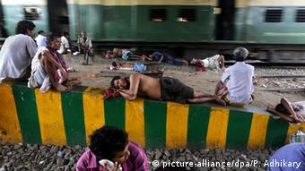 Indian commuters and labours rest under a bridge on the railway track during a heatwave while temperatures reached 42 degrees Celsius in Calcutta, India, 22 May 2014 (Photo: EPA/PIYAL ADHIKARY)