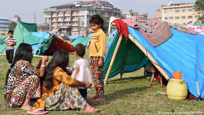 Disaster-affected people stay in a tent in a vacant lot in Kathmandu on May 25, 2015, one month after a killer earthquake hit Nepal.