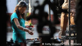 A Nepalese resident makes offerings at a temple in Kathmandu on May 25, 2015 as the country marks one month since a deadly earthquake struck the country, killing more than 8,600 people.