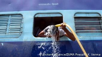 An Indian commuter uses the train water pipes to bath at railway station in Allahabad. Most of north India has been reeling under heat wave conditions with temperature soaring to over 46 degree Celsius