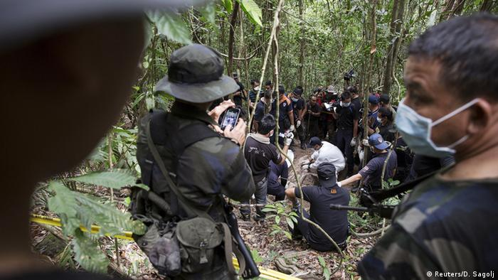 Policemen monitor as forensic experts dig out human remains near the abandoned human trafficking camp in the jungle close the Thailand border at Bukit Wang Burma in northern Malaysia May 26, 2015.