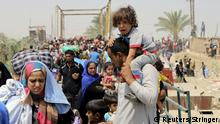 24.5.2015 *** A displaced Sunni man fleeing the violence in Ramadi carries a crying child on his shoulders, on the outskirts of Baghdad, May 24, 2015. Iraqi forces recaptured territory from advancing Islamic State militants near the recently-fallen city of Ramadi on Sunday, while in Syria the government said the Islamists had killed hundreds of people since capturing the town of Palmyra. REUTERS/Stringer