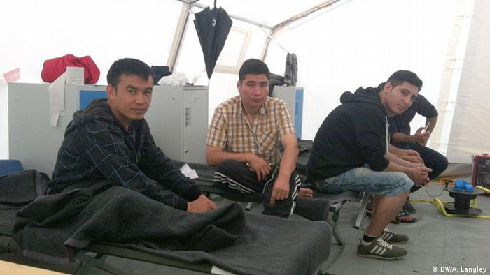 Three men sit in the tent that has become their home in Linz