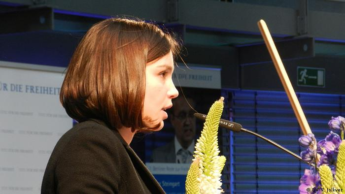 Zhanna Nemtsova seen from the right side speaking in front of a microphone. Photo: Nikita Jolkver