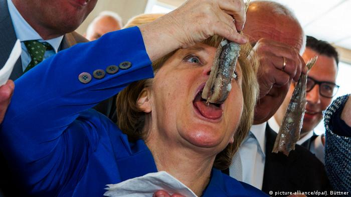 Angela Merkel eating a herring on a trawler. Archive photo from 2015. (picture-alliance/dpa/J. Büttner)