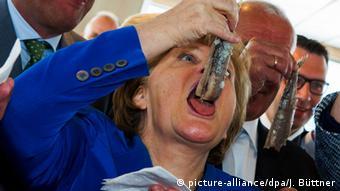 Ангела Меркель дегустирует маринованную сельдь