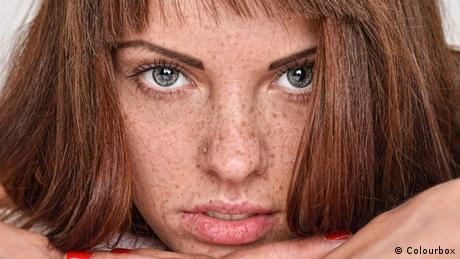 Frau mit roten Haaren und Sommersprossen im Bett