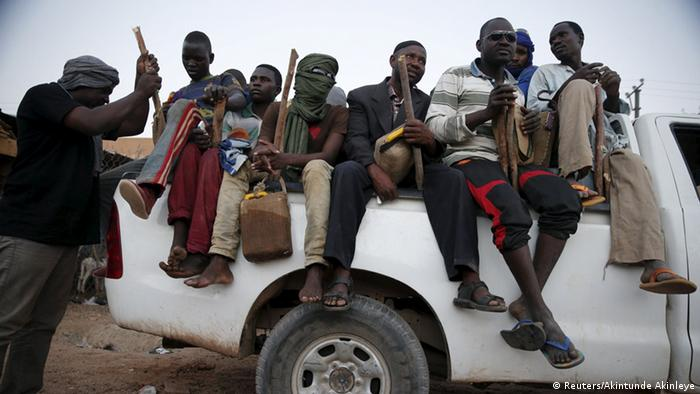 people sitting on back of a pick-up (Reuters/Akintunde Akinleye)