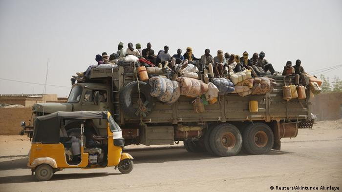 Migrants loaded on top of a lorry.