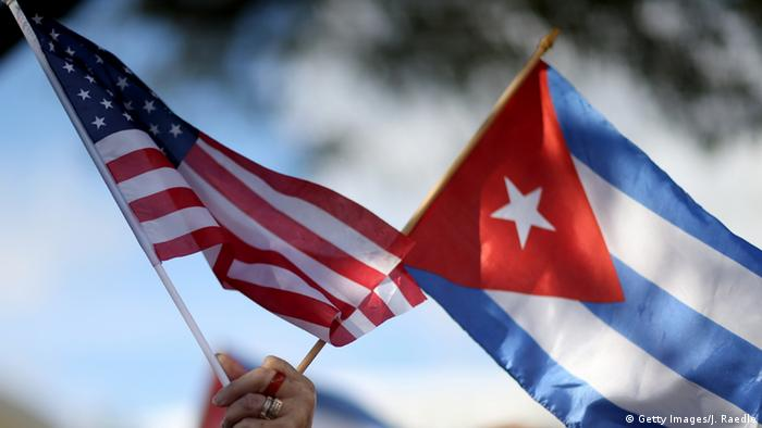 A hand holding up a Cuban and an American flag Photo: Joe Raedle/Getty Images