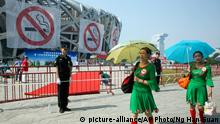 Square dance performers walk past anti-smoking banners displayed on the iconic Bird's Nest National Stadium on World No Tobacco Day in Beijing Sunday, May 31, 2015. Beijing plans to introduce new regulations on June 1 requiring all indoor public places - and many outdoor public places - to be 100% smoke-free. (AP Photo/Ng Han Guan)