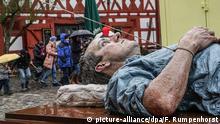 Eine überlebensgroße, lebensecht wirkende Figur des britischen Künstlers Sean Henry liegt am 29.03.2015 in Neu-Anspach (Hessen) bei Regenwetter auf dem Marktplatz des Freilichtmuseums Hessenpark. Das Kunstwerk ist Teil der in diesem Jahr hier stattfindenden Skulpturenbiennale Blickachsen 10. Foto: Frank Rumpenhorst/dpa