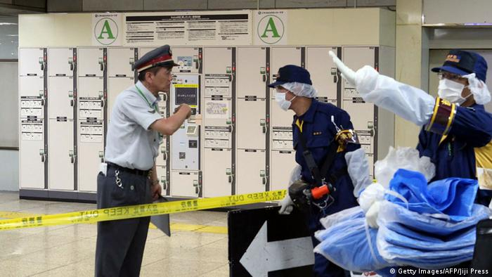 This picture taken on May 31, 2015 shows police officers and a station employee putting up a Keep Out sign at a locker storage room as they inspect a locker at the Tokyo station. The corpse of a woman that had been stuffed in a suitcase and left in a locker at one of the world's busiest train stations went undiscovered for a month.