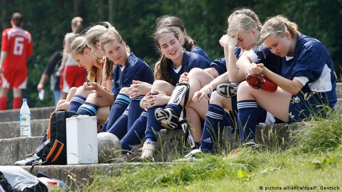 German girls at a soccer match wait on the sidelines