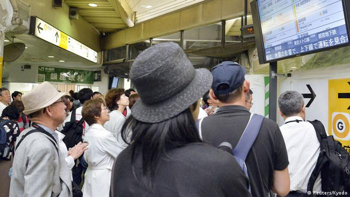 Passengers check train schedules after train services were suspended following an earthquake at the Shinbashi station in Tokyo (Photo: REUTERS/Kyodo)