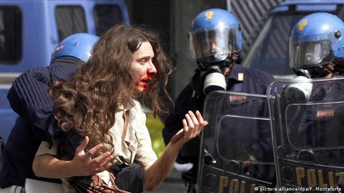 Bleeding protester being led away by police at the G8 Summit in Genoa in 2001 (picture-alliance/dpa/F. Monteforte)