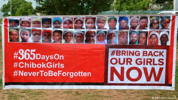 A large poster showing faces of some of the kidnapped schoolgirls and hashtags including #BringBackOurGirls