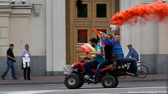 LGBT acitivsts drive by Moscow's mayor office holding a flare and rainbow flag riding on a quad-bike during an unauthorized gay rights activists rally