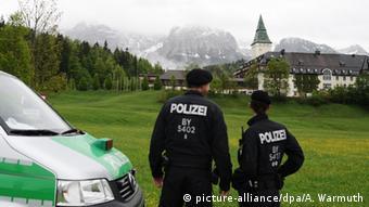 Zwei Polizisten stehen neben einem Einsatzfahrzeug und schauen auf Schloss Elmau. (Foto: picture-alliance/dpa/A. Warmuth)