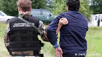 Литовский пограничник задерживает нелегального мигранта