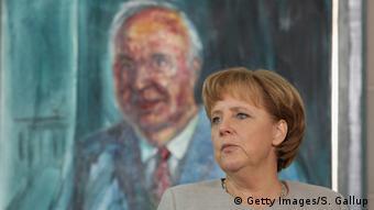 Μπροστά σε πορτρέτο του πολιτικού της μέντορα Χέλμουτ Κολ