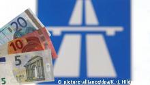 ILLUSTRATION - Verschiedene Euro-Banknoten werden am 25.03.2015 an einer Autobahnauffahrt bei Nesselwang (Bayern) vor ein Hinweisschild gehalten. Foto: Karl-Josef Hildenbrand/dpa (zu: Bundestag soll Pkw-Maut am Freitag beschließen vom 25.03.2015)