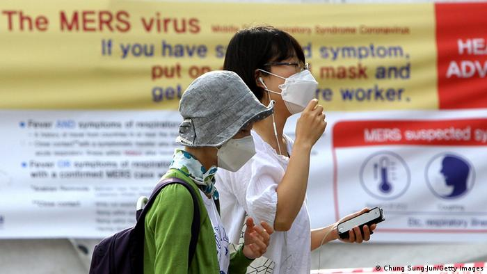 Visitors wearing masks walk in front of a health advisory sign about the MERS virus at a quarantine tent for people who could be infected with the MERS virus at Seoul National University Hospital on June 2, 2015 in Seoul, South Korea (Photo: Chung Sung-Jun/Getty Images)