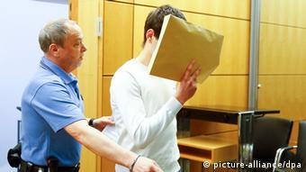 Sanel M. in court with a folder covering his face. (Photo: Kai Pfaffenbach/Pool Photo via AP)