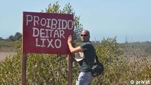 September 2014 Der mosambikanische Jurist und Anwalt Carlos Serra Júnior ist einer der bekanntesten Umweltschützer des Landes. Er setzt sich besonders für den Erhalt der Wälder des Landes ein. Außerdem hat er mehrere Kampagnen für saubere Strände durchgeführt. Auf dem Foto ist er an einem Strand in Mosambik mit einem Schild zu sehen, auf dem steht Proibido deitar lixo (Müll abladen verboten); Copyright: privat