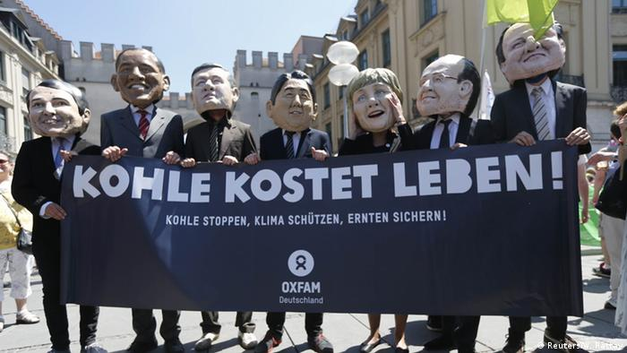 Protesters wearing masks of G7 leaders holding a banner reading Coal costs lives.
