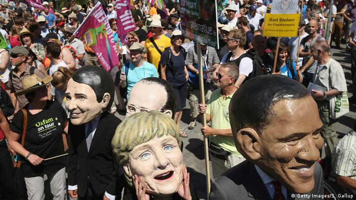 Protesters masked as Angela Merkel and Barack Obama in front of crowd of demonstrators.