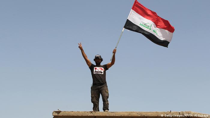 man holding flag copyright: AHMAD AL-RUBAYE/AFP/Getty Images