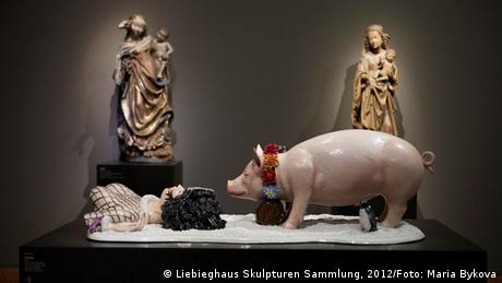 Jeff Koons, Fait d'hiver, scuplture with pig and female torso, two sculptures of Mary and Jesus in the background