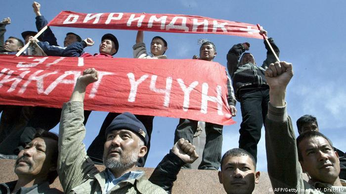Männer in Kirgistan halten Plakte hoch und recken ihre Fäuste in die Luft (Photo: VIKTOR DRACHEV/AFP/Getty Images)