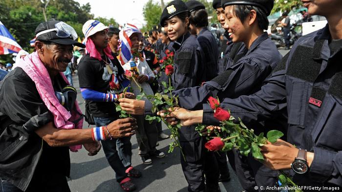 Thai anti-government protesters greet and receive flowers from policewomen after protesters crossed barricades in Bangkok on December 3, 2013