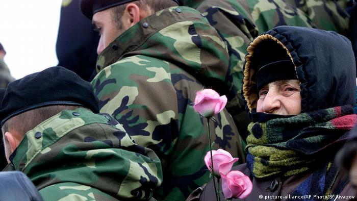 Demonstration in Tiflis, eine ältere Frau mit Schal hinter Soldaten hält Rosen in der Hand (AP Photo/ Shakh Aivazov)
